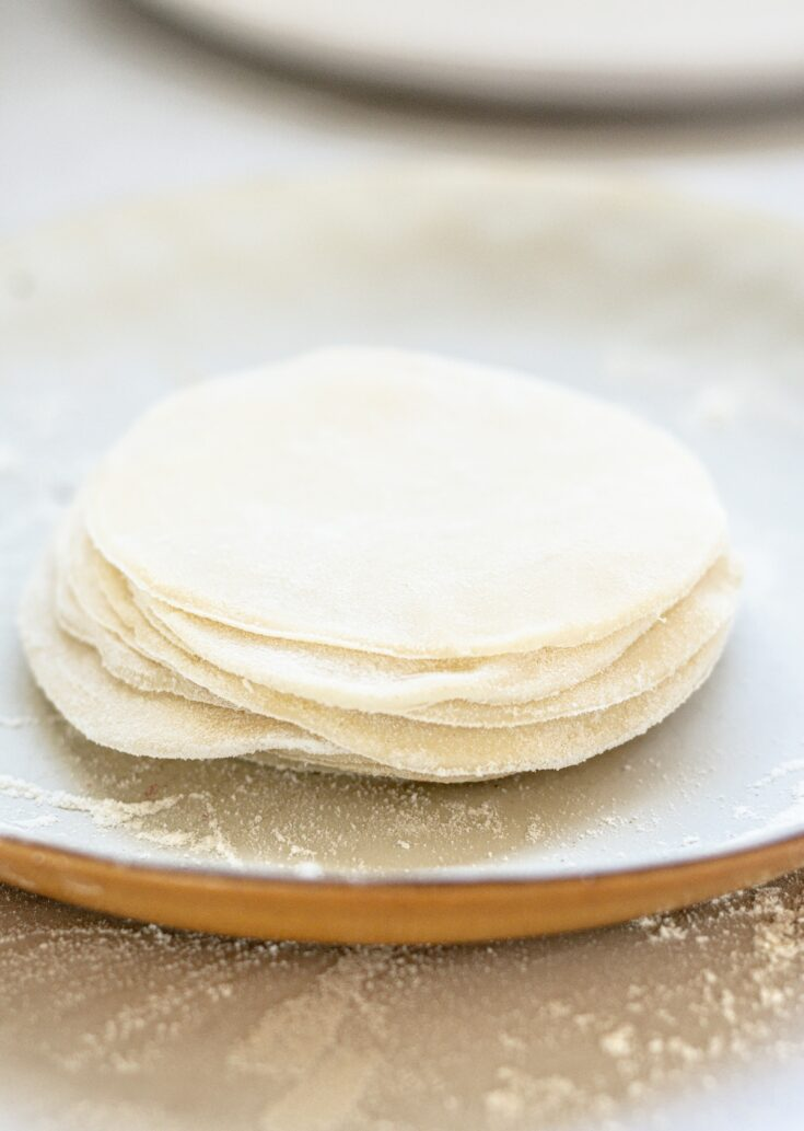 a stack of dumpling wrappers on a white plate